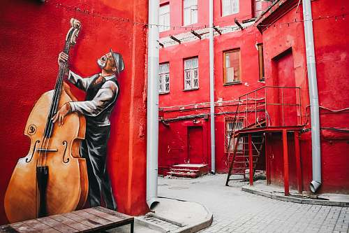 person man playing cello mural girl