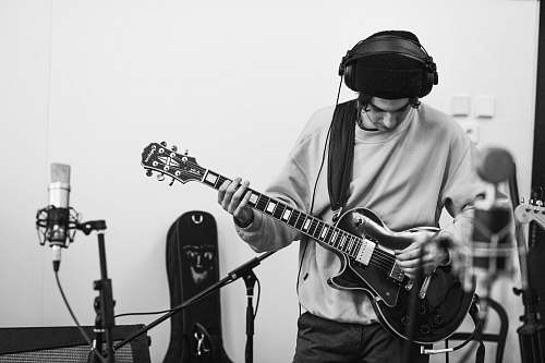 people man playing guitar inside a studio black-and-white