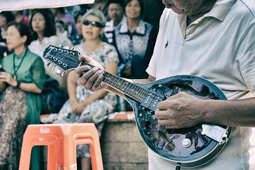 person man playing string instrument near croud people