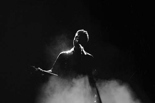 person man singing on stage in grayscale photography black-and-white