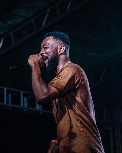 person man singing on stage white wearing brown crew-neck shirt people