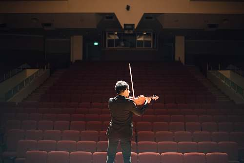 person man standing in front of stage playing violin people