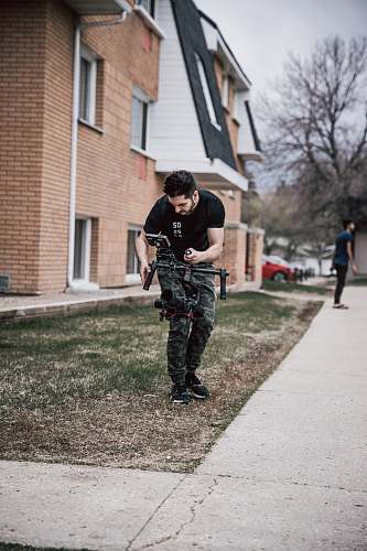 person man using drone standing in green field clothing