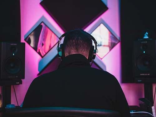 person man wearing black headphones near two PA speakers people