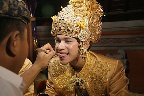 person man wearing gold head dress opening his mouth people