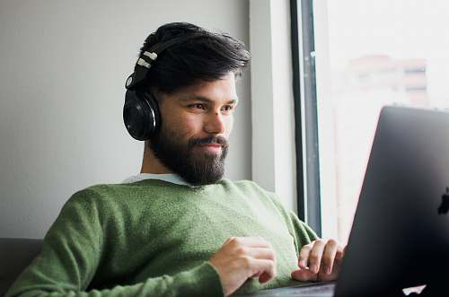 person man wearing headphones while looking at MacBook face