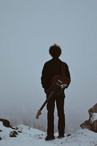 person man with guitar on his back standing on cliff people