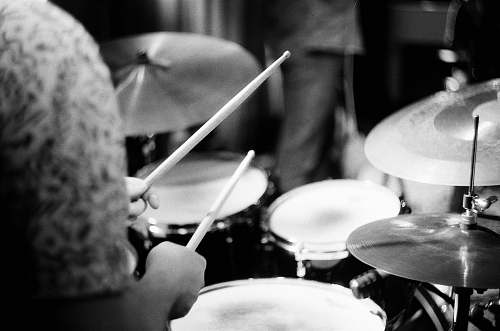 black-and-white person playing drums musical instrument