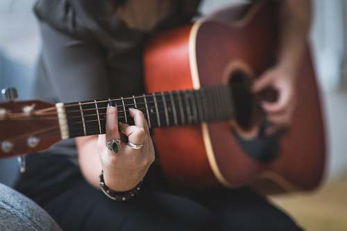 music person sitting while using guitar guitar