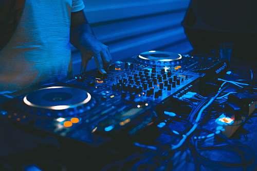 music person using black DJ controller dj