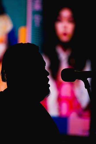 audience silhouette photography of man in front of a microphone crowd