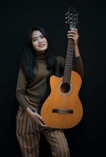 person smiling woman while holding cut-away acoustic guitar people