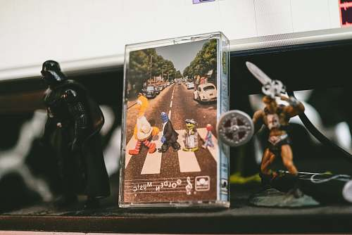 person two He-Man and Darth Vader figurines on table people