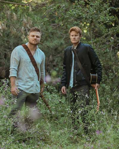 person two men with guitars standing in forest plant
