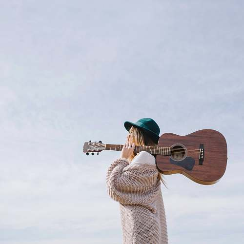 person woman carrying brown acoustic guitar people