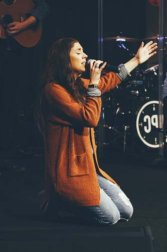 person woman kneeling while holding microphone apparel