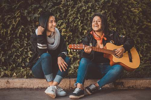 person woman playing guitar sitting beside with woman wearing scarf people