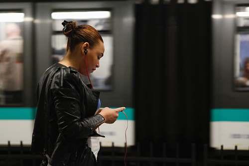 person woman using phone near train apparel