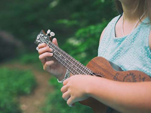 music woman wearing blue sleeveless top holding brown ukulele person