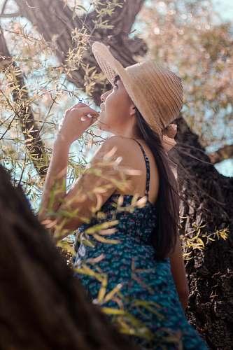 person woman wearing gray sun hat beside tree people