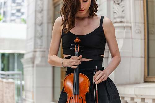 person women holding a violin during daytime violin