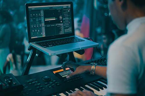 colombia person playing electronic keyboard while recording computer