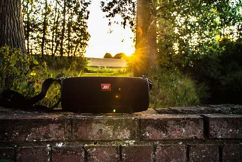 rest black JBL portable speaker on brick bench brick wall