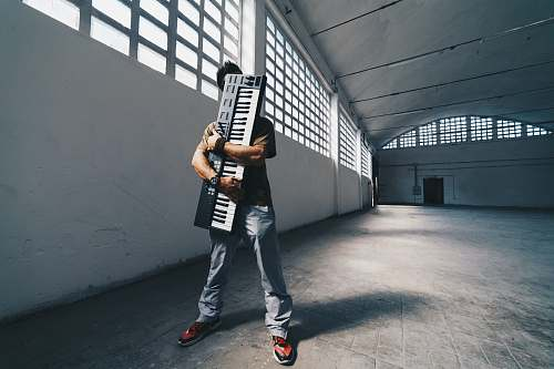 grey man hugging the electronic keyboard while standing inside room accordion