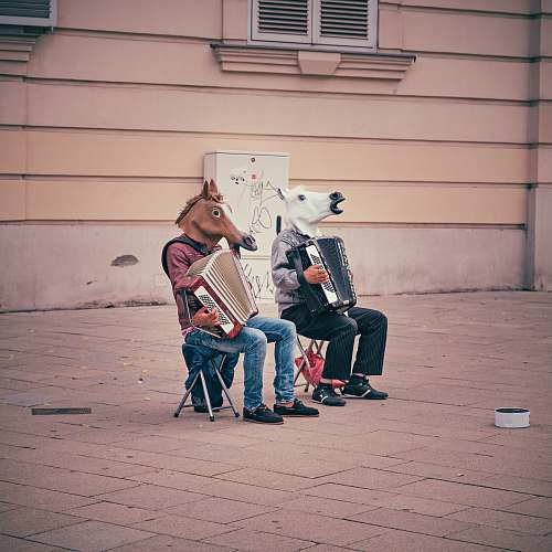 music two person wearing horse heads sitting on folding chairs while playing accordions beside brown concrete building accordion