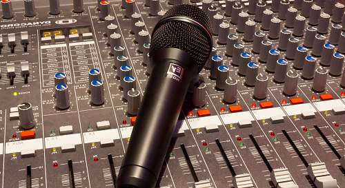 microphone black wireless microphone on grey and multicolored audio mixer mixing console