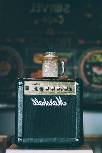 jar black Marshall guitar amplifier with glass mug on top filled with beverage coffee