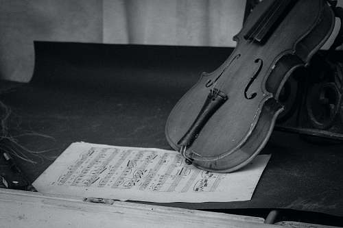 black-and-white grayscale photography of violin on table with music sheet grey