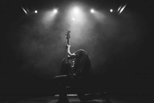 black-and-white lead guitarist doing guitar show on stage grey