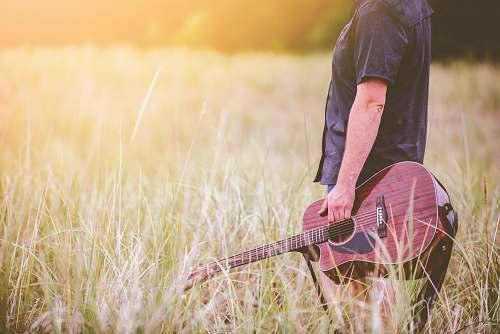 grass man carrying brown cutaway acoustic guitar standing on green grass field guitar player