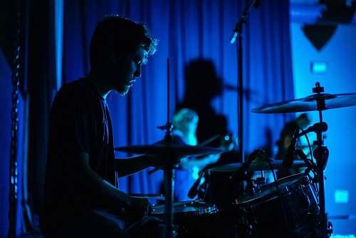 blue man playing drum set drummer
