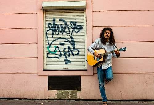 human man playing guitar on street during daytime people
