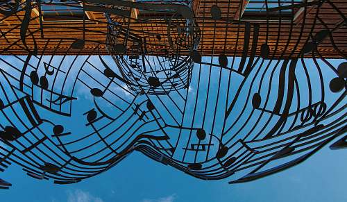 blue musical notes themed metal artwork under blue sky at daytime art