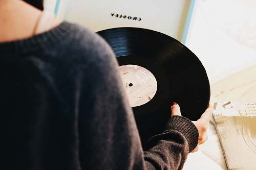 record person holding black vinyl record hand