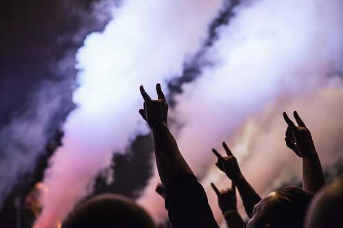 finger photo of persons doing rock hand sign festival
