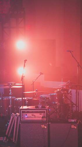 concert red drum set besides microphone stands audience