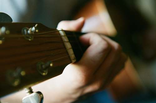 guitar selective focus photography of person playing guitar musician