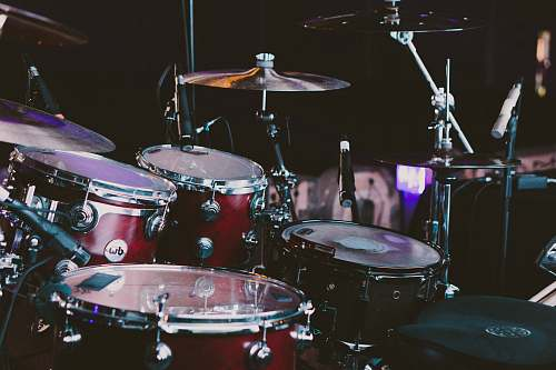drum selective focus photography of red drum set musical instrument
