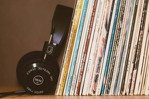 retro wireless headphones leaning on books vintage