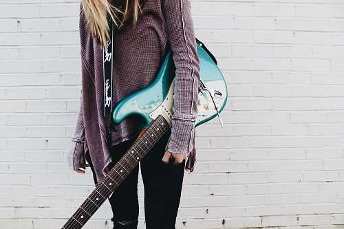 guitar woman carrying green stratocaster guitar musician