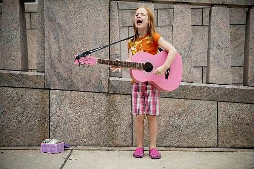 human girl playing guitar near wall person