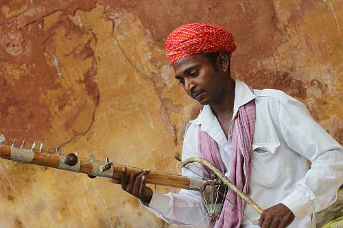 human man in red turban playing musical instrument person