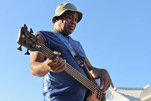human man playing electric bass guitar person
