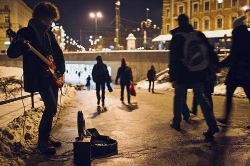 person man playing guitar on street during nighttime human
