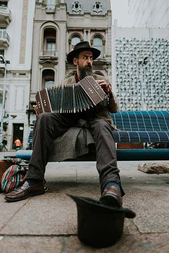human man sitting on bench playing accordion music