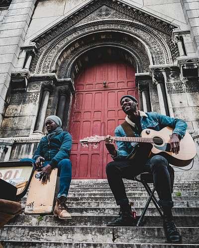 person man wearing blue denim jacket playing cutaway guitar human